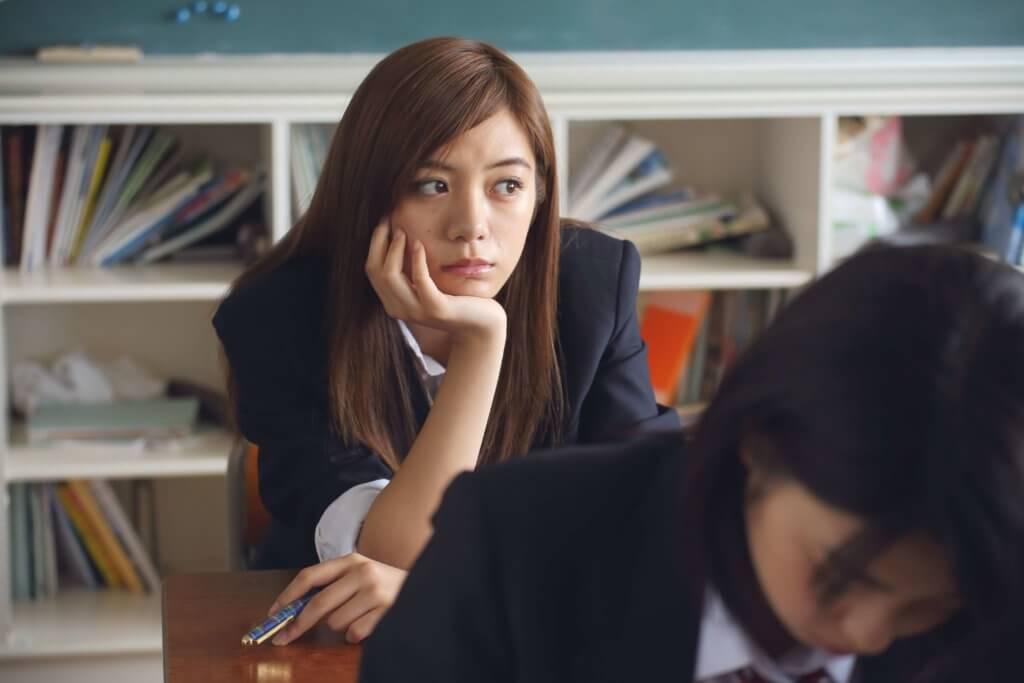 Junge Frau sitzt an einem Tisch und guckt nachdenklich und träumend, etwas frustriert aus dem Fenster