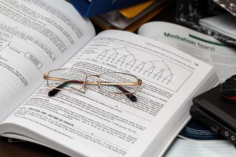 Buch mit Brille auf einem Arbeitstisch