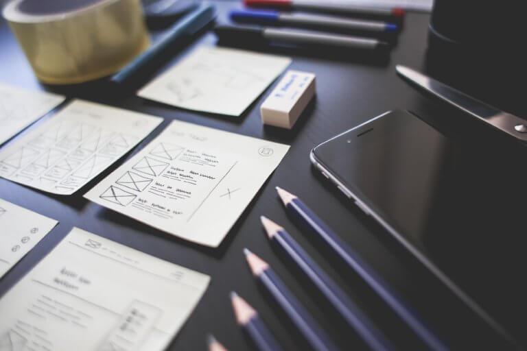 Kontrollzettel, Bleistifte und ein Handy liegen auf einem Tisch.