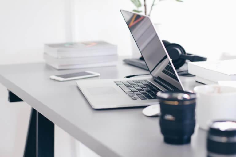 Laptop, Kaffeetasse und Papier liegt auf einem Tisch zur Korrektur von Bachelor oder Masterarbeiten.
