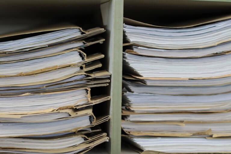 Dokumente liegen übereineander, Akten stapeln sich übereinander in einem Regal