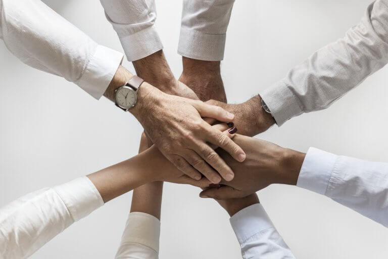 8 Hände liegen übereinander - Zusammenhaltsaudruck