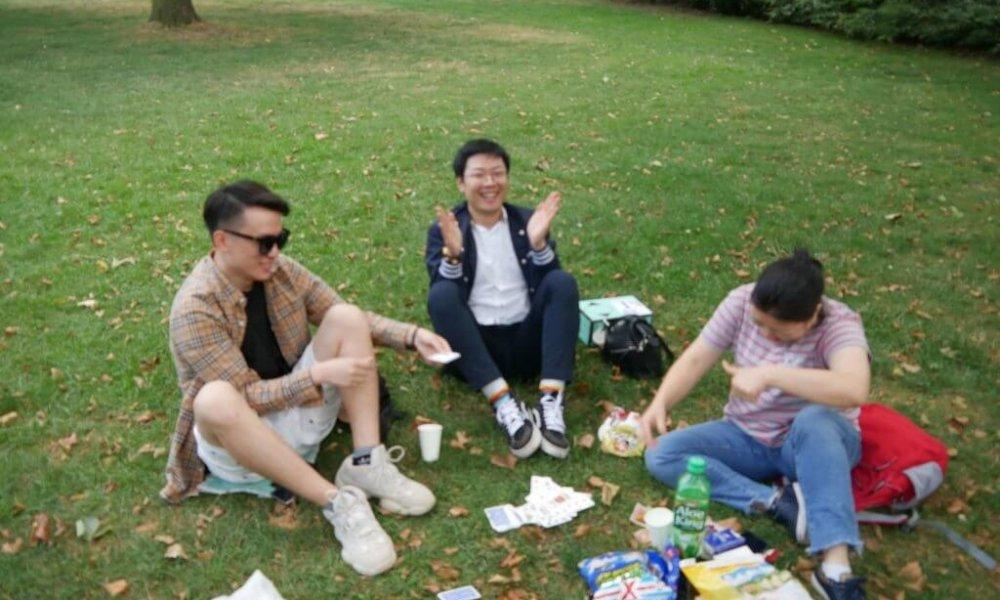 Drei Personen sitzen auf einer Wiese und klatschen vor Freude und lachen.