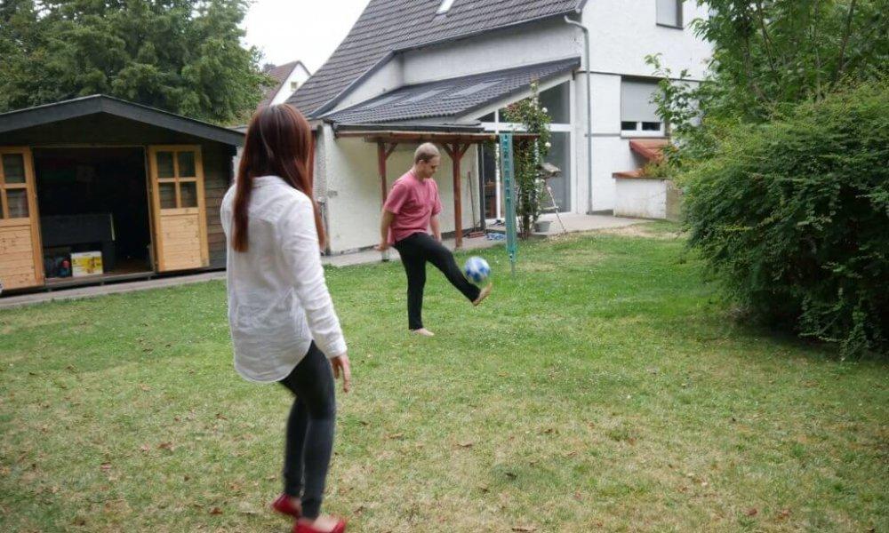 Zwei Personen spielen Fußball auf einer Wiese.