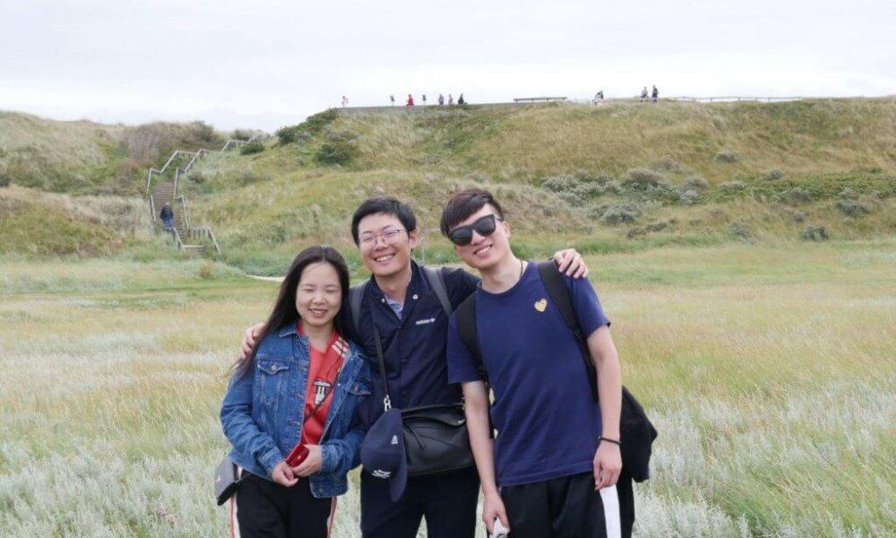 Ausflug nach Texel am Strand, drei Personen umarmen sich und lachen in die Kamera.