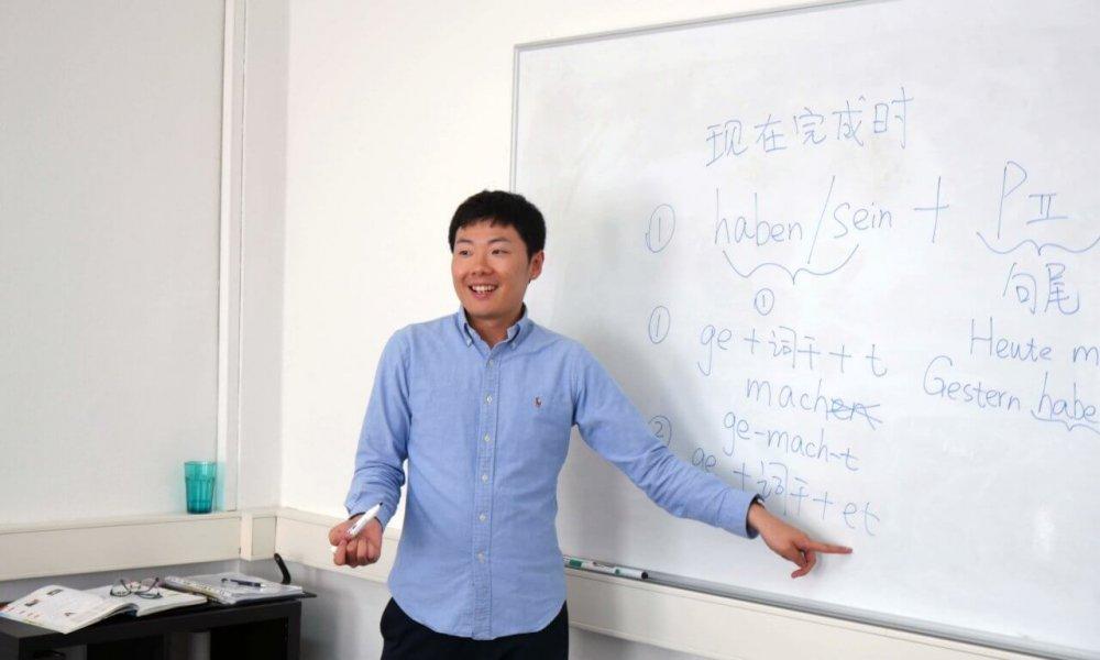 Lehrer veranschaulicht etwas in einem Sprachkurs an einem Whiteboard.